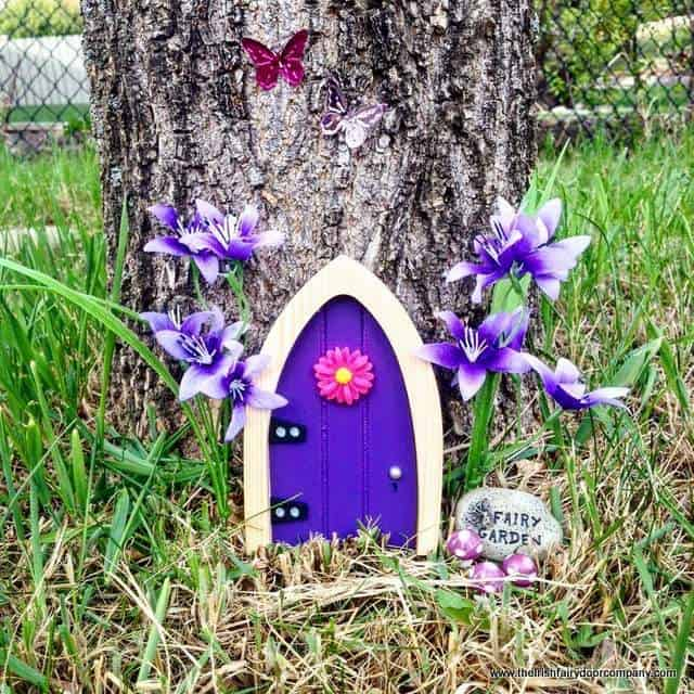 Purple fairy door by a tree with a pink decorative flower