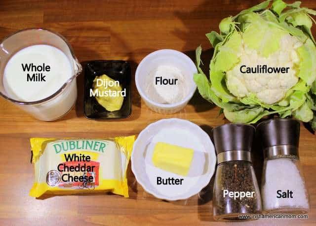 Measured ingredients for cauliflower cheese including milk, mustard, flour, cauliflower, butter, cheese, salt and pepper