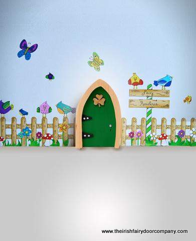 Green Irish fairy door with shamrock on a wall with a fence, birds and butterflies