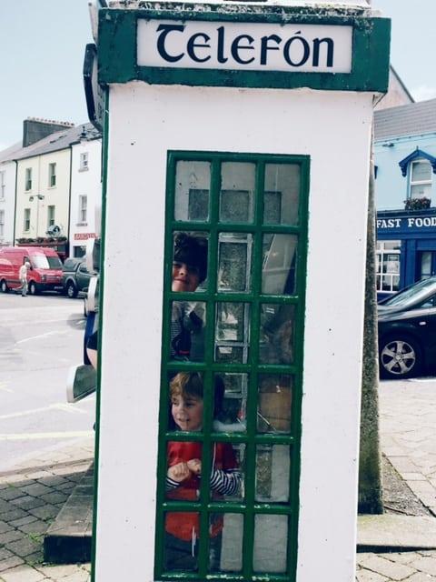 Green and cream old Irish phone box with kids inside