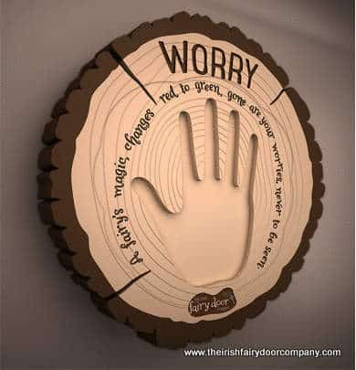 Child\'s hand print on a magical worry plaque shaped like a tree slice