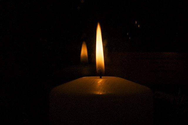 Dark background showing the reflection of a candle flame