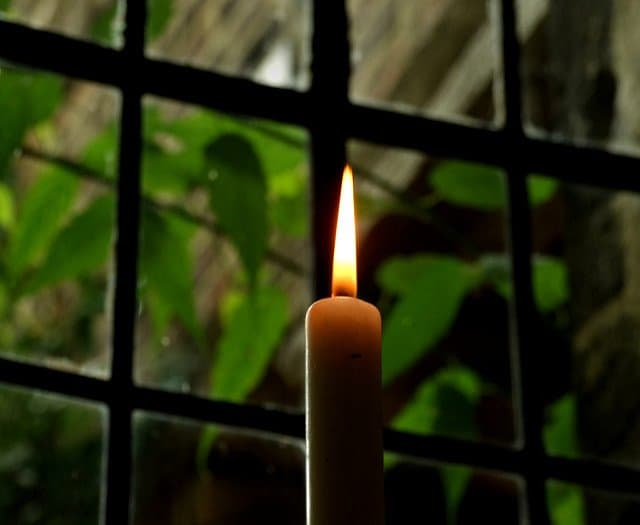 Yellow candle flame glowing in a paneled window