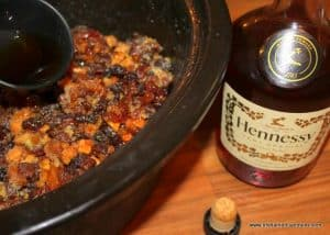 A bottle of Hennessy brandy beside a crockpot of mincemeat pie filling