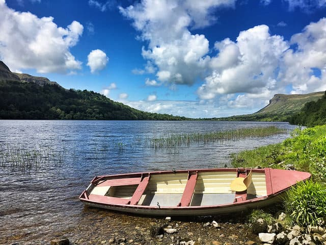 A small boat beside a lake with reeds and a mountain in the background
