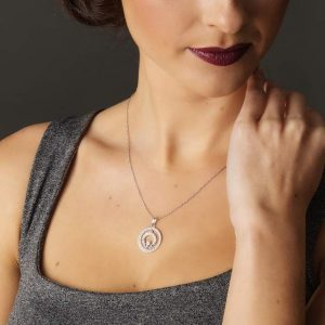Female model wearing an Irish Swarovski Crystal Claddagh pendant on a silver chain