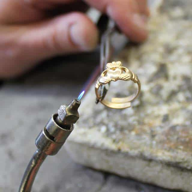 A skilled jeweler using a hot torch to shape and form a Claddagh ring