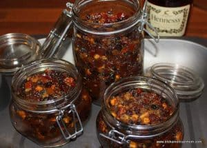 three mason jars filled with homemade mincemeat with a bottle of brandy in the background