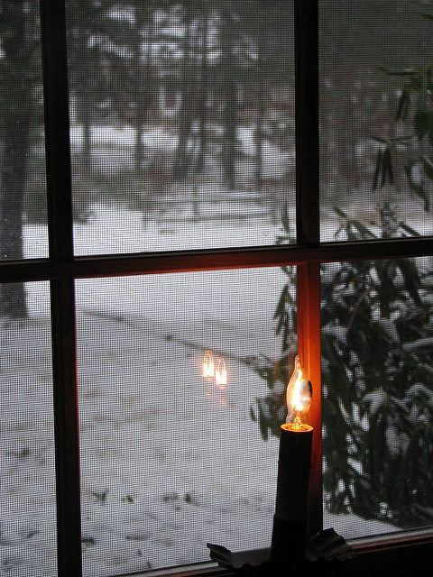 Battery operated candle in a window with snow outside