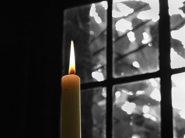 White candle with a yellow flame contrasting with a black and white window