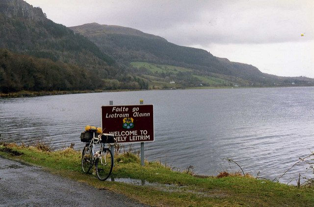 A bicycle is parked against a sign next to a body of water and a mountain in the background