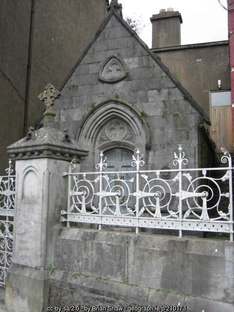 An old stone building with a wall and railing