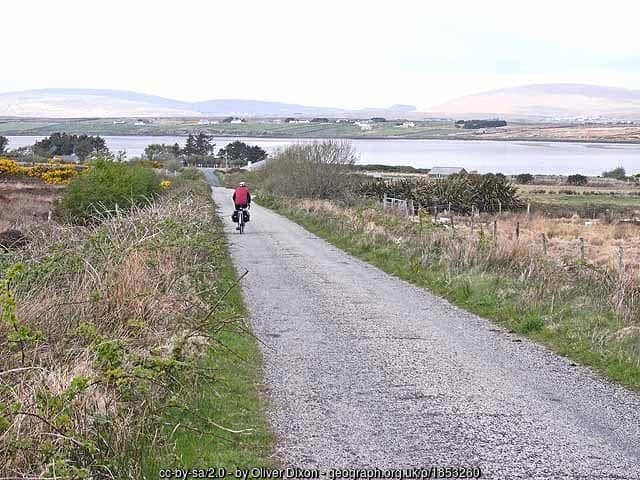 A cyclist on a country road on the coast of Ireland