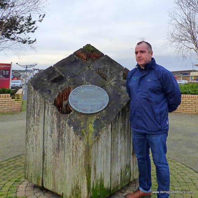 A man holding posing for the camera beside a stone marker