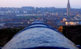 Looking out over a cannon and the Derry city walls