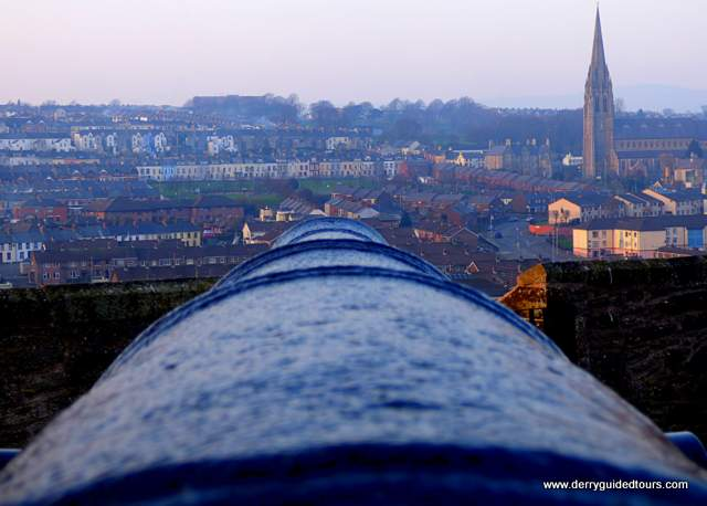 Looking out over a cannon toward distant buildings