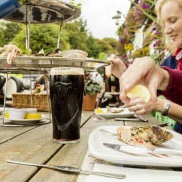 A pint of stout on a wooden table as a lady squeezes a lemon over salmon