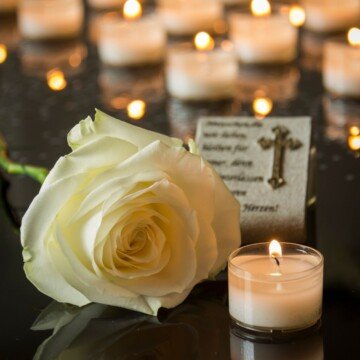 A white rose, a candle and a religious plaque on a black marble surface in front of rows of lighting candles