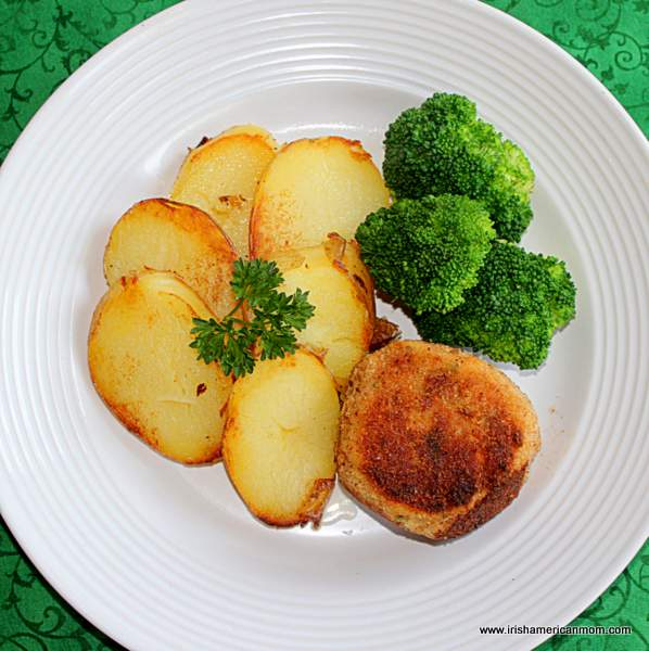 Fried potatoes, broccoli and a salmon cake on a white dinner plate