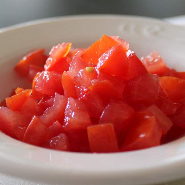 Pieces of diced tomatoes in a white bowl.