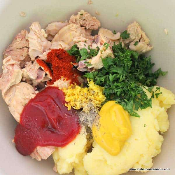 Salmon, ketchup, mustard, mashed potatoes and parsley in a bowl