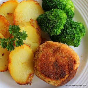 A plate of food with broccoli, salmon cakes and fried potato slices