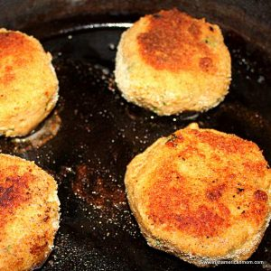 Salmon cakes sizzling in a cast iron pan