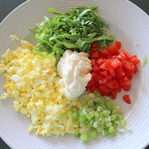 Ingredients for egg salad sandwich filling on a white plate