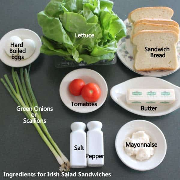 Ingredients for making Irish salad sandwiches including bread, butter, hard boiled eggs, tomatoes, lettuce and mayonnaise.