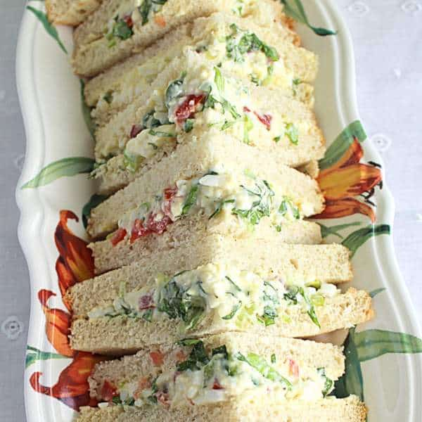A row of triangular tea sandwiches on a plate