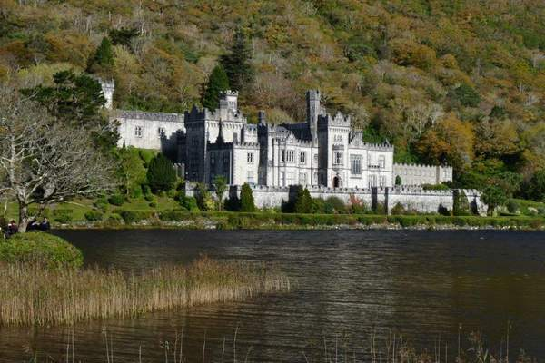 A castle surrounded by a body of water with trees in the background