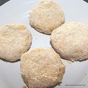 Salmon cakes ready for frying with bread crumb coating on a white plate