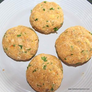 Four salmon fish cakes shaped into patties on a white plate