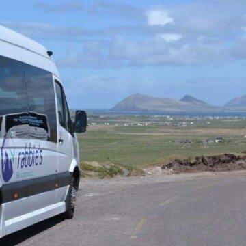 A tour bus on a road in a mountainous landscape