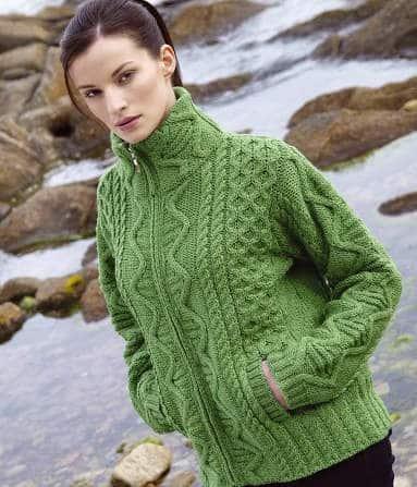 A woman in a green sweater n a rocky beach