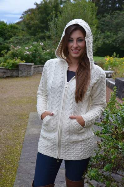 A person standing posing for the camera wearing a zipped cardigan