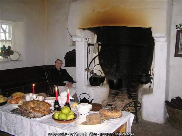 A woman beside a fire and a table laid with food