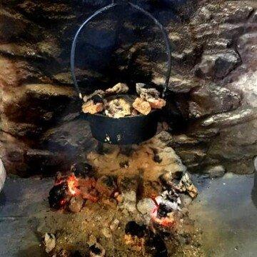 A cast iron pot hanging over an open fire