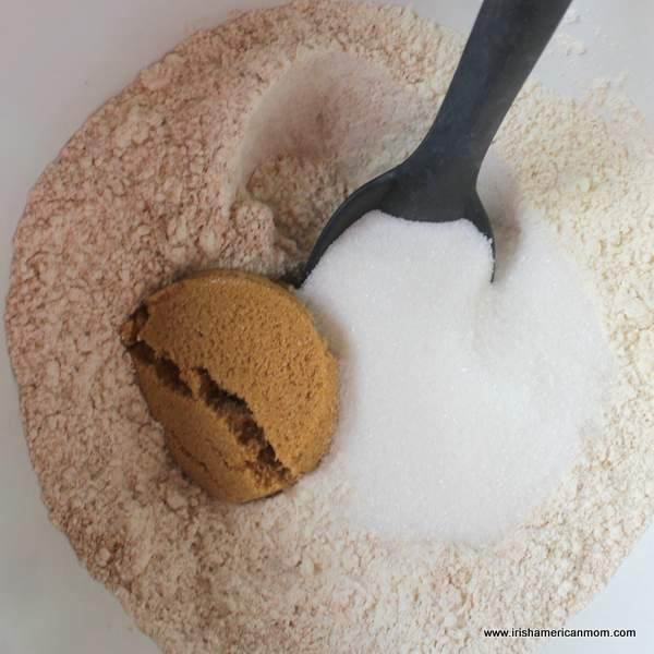 Flour with brown and white sugars in a bowl with a black spoon