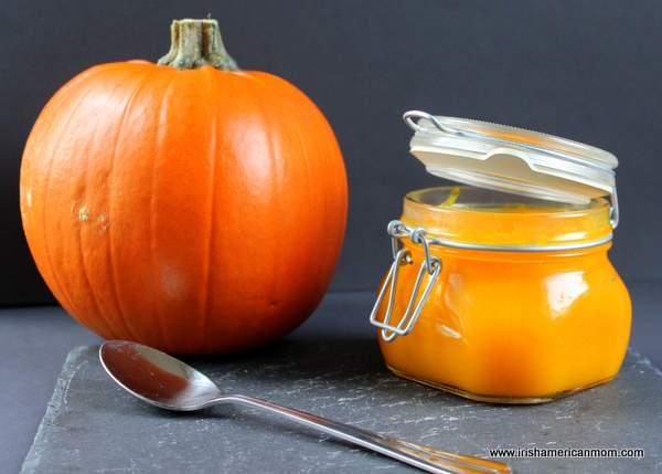 A whole pumpkin beside a mason jar of homemade pumpkin puree