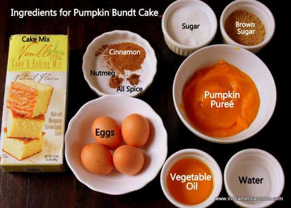 Ingredients for pumpkin cake including spices, cake mix, eggs, pumpkin puree, sugar, oil and water