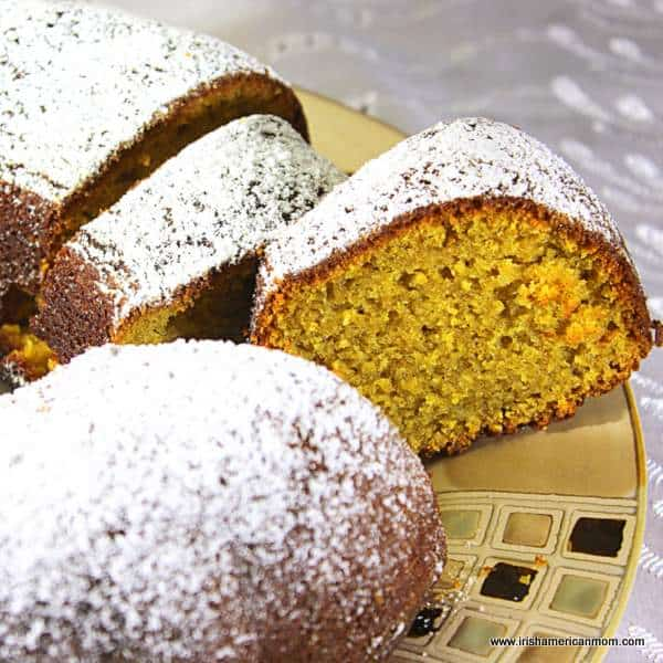 A bundt cake on a plate covered in powdered sugar