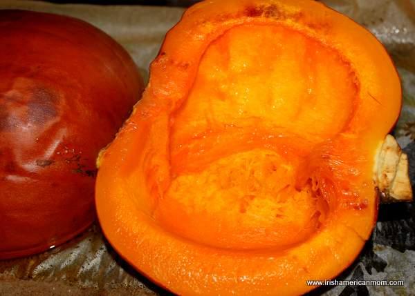 Half of a roasted pumpkin on a baking sheet
