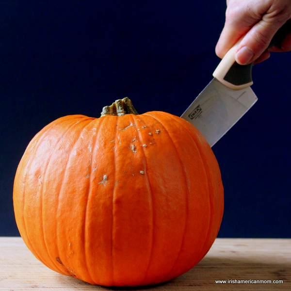 A knife cutting through a pumpkin