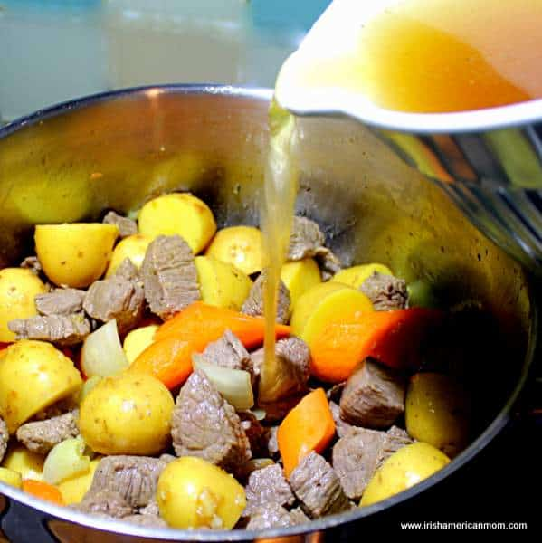 Beef broth being added to a pot of stew