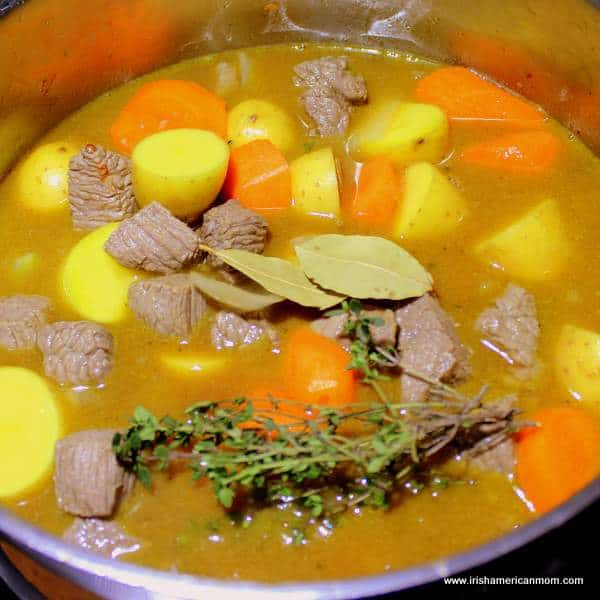 herbs in a pot of stew with meat, potatoes and carrots