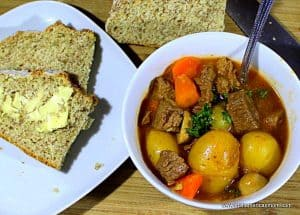 A bowl of stew with a spoon beside a plate of buttered soda bread