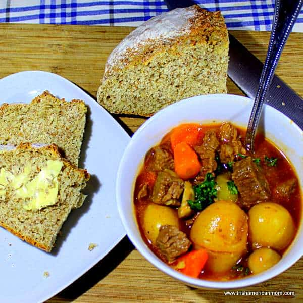 A bowl of meat and potato stew on a cutting board beside a plate with buttered slices of wholewheat bread and an uncut farl of brown soda bread