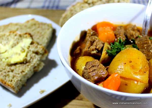 Beef stew served in a white bowl with buttered whole wheat soda bread
