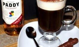 Irish coffee shown beside a bottle of Paddy Irish whiskey